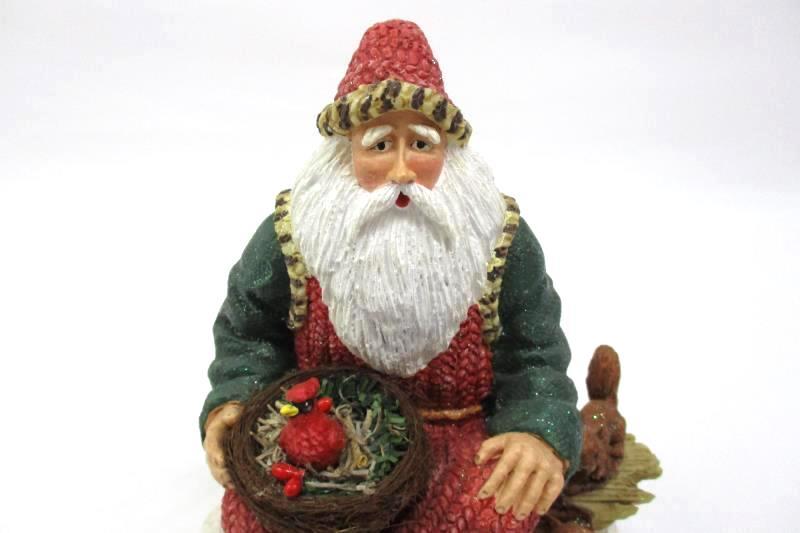 Bisque Santa Sitting On A Log Holding A Cardinal Nest Figurine